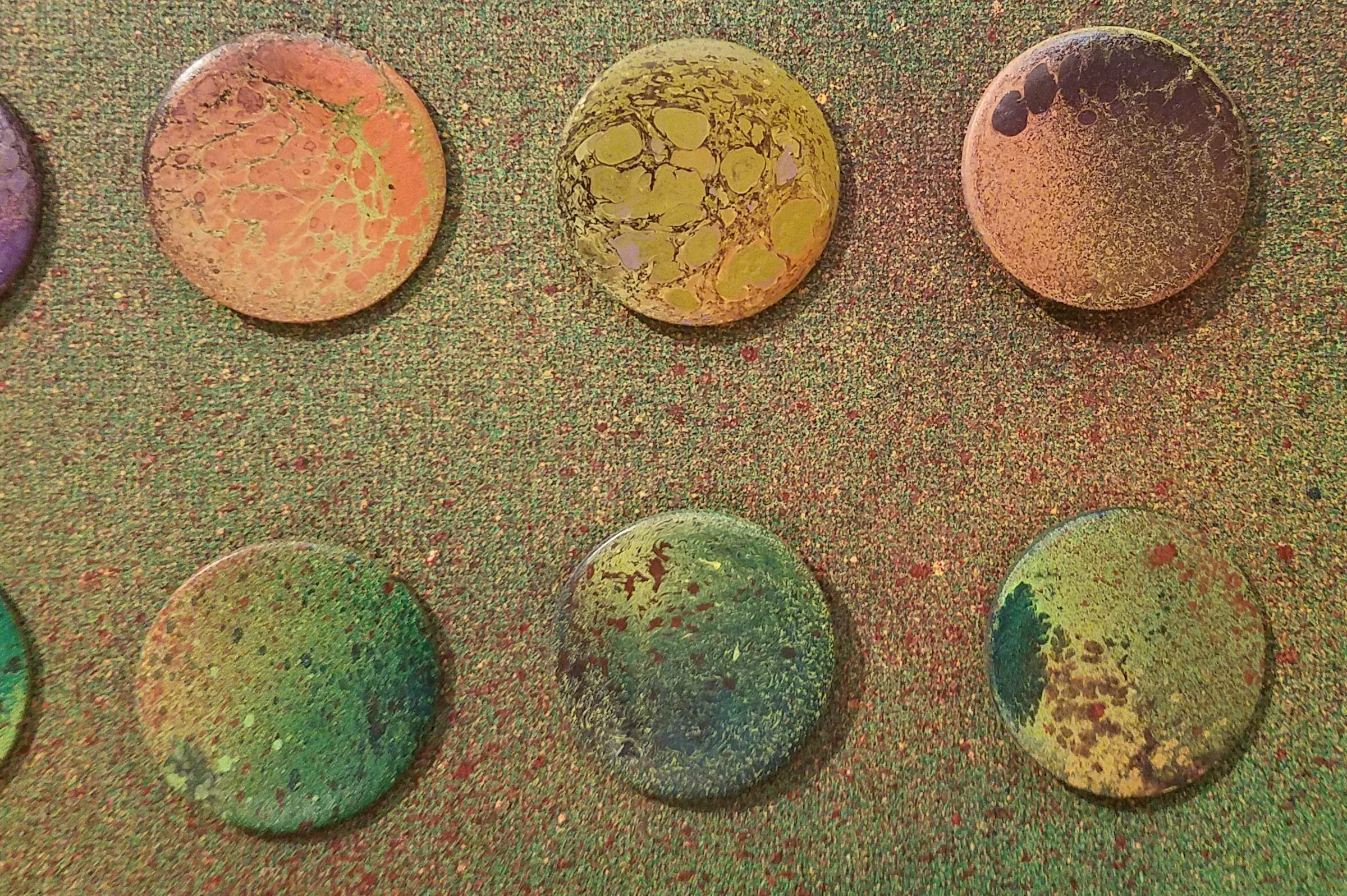 Circular spray painted recycled pins